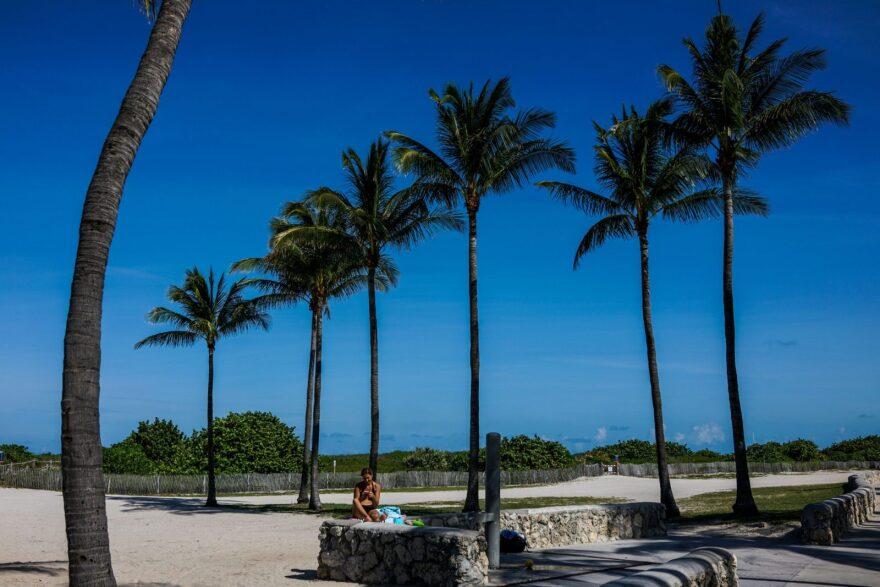 A woman takes in the sun near a closed beach in South Beach, Miami.