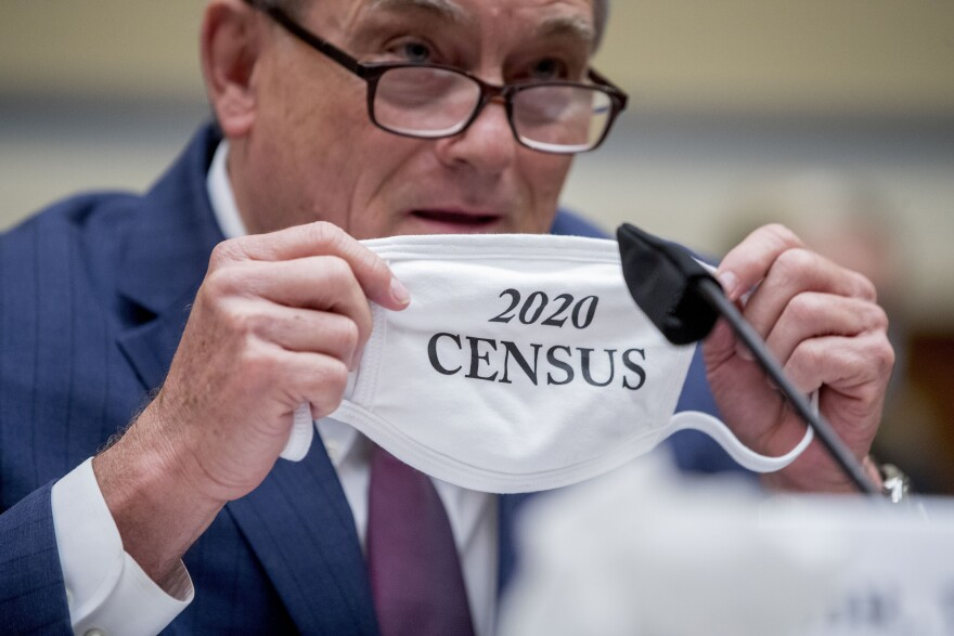 """Census Bureau Director Steven Dillingham holds up his mask with the words """"2020 Census"""" as he testifies before a House Committee on Oversight and Reform hearing on the census in July."""