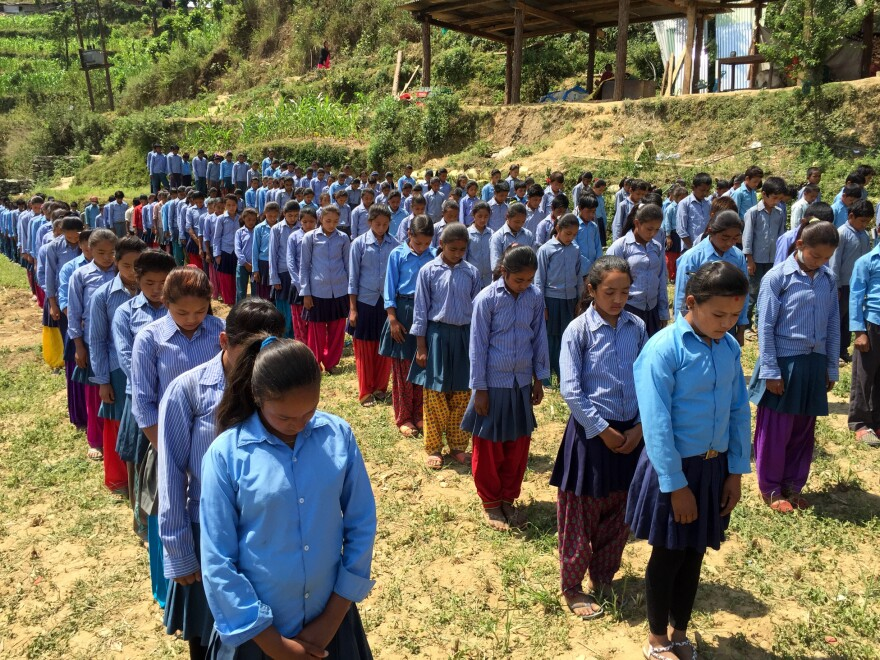 Schoolchildren in a Nepali village stand in a cornfield and observe a moment of silence to remember earthquake victims.
