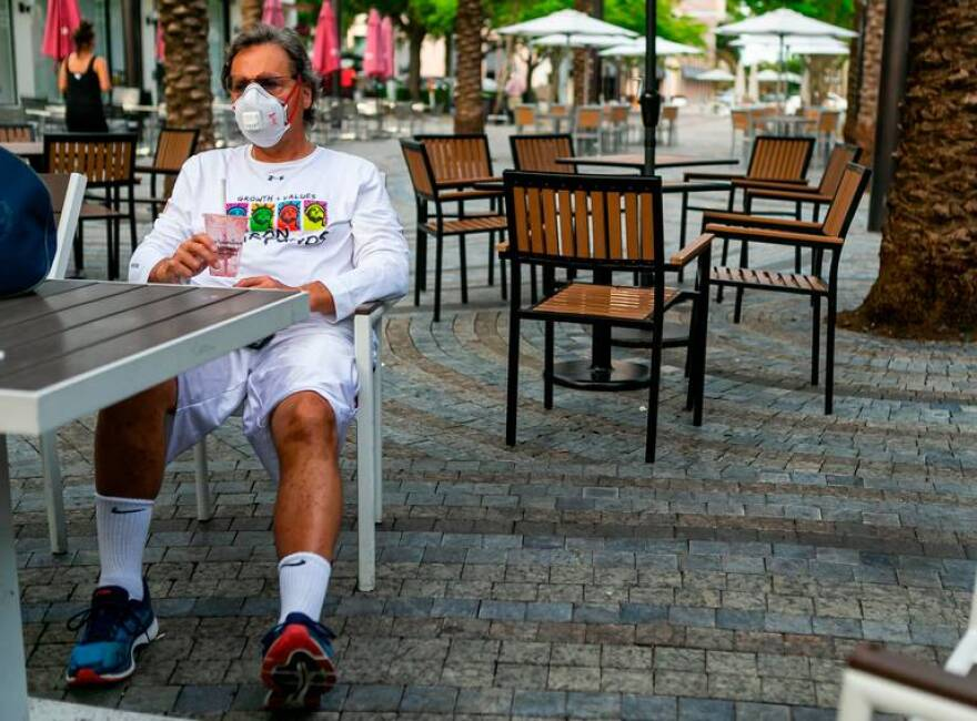 A man wearing a mask sits outdoors at a restaurant.