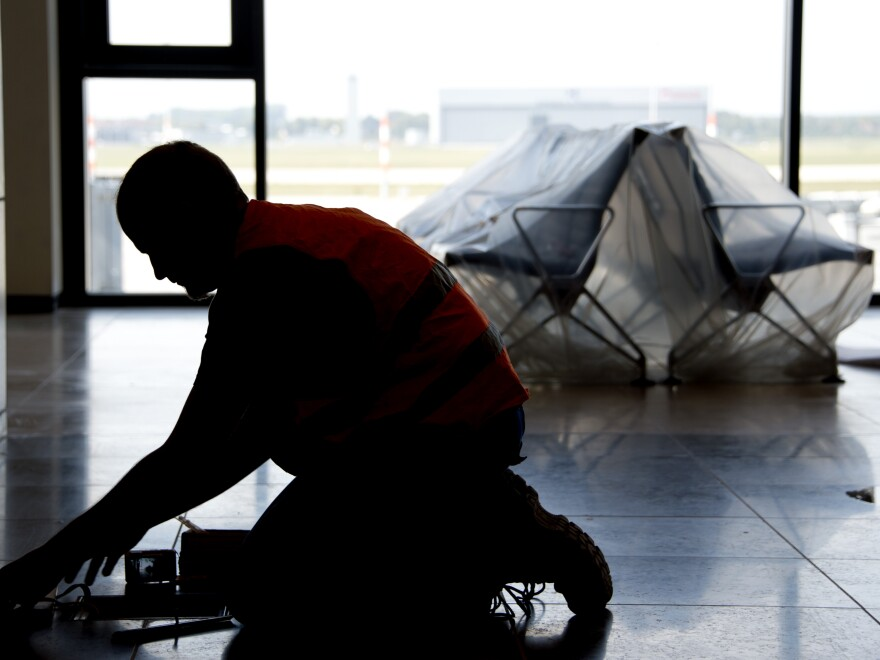 A carpenter works in the unfinished departure hall of the airport on Sept. 11.