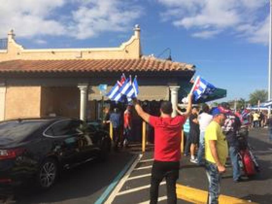 A man sells Cuban flags during an impromptu celebration of Fidel Castro's death outside La Carreta, a Cuban restaurant in Westchester.