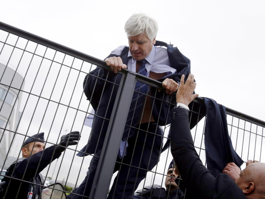 Security and police officers help Pierre Plissonnier, an executive in Air France's long-haul flight unit, to climb over a fence after several hundred employees stormed into the offices of Air France on Monday.