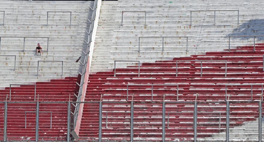 A River Plate fan sits on an empty stand at the Monumental Stadium in Buenos Aires, after the all-Argentine Copa Libertadores second leg final match against Boca Juniors was postponed on Sunday for the second time following an attack on the Boca team bus by River fans.