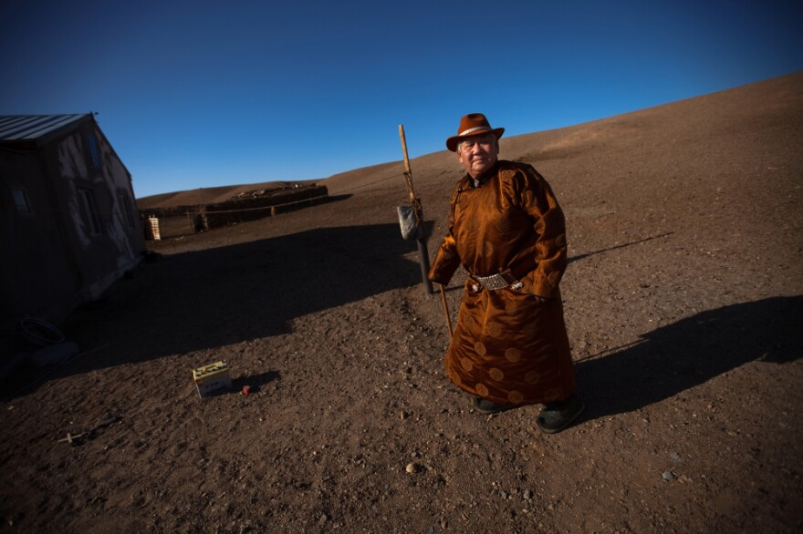 Herder Mijiddorj Ayur, 76, stands outside his home in South Gobi, Mongolia. He worries about the effects a local mine will have on his livelihood.