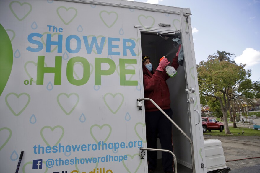 Lisa Marie Nava cleans a mobile shower provided by The Shower of Hope in MacArthur Park in Los Angeles on March 23, 2020.