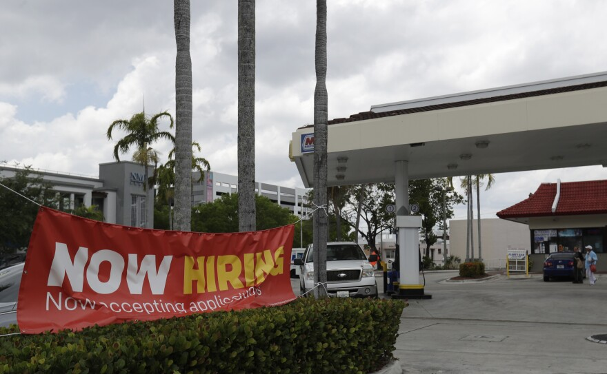 "A big banner is tied up on trees. It reads, ""Now hiring. Now accepting applications."" Besides the banner is what looks to be a gas station."