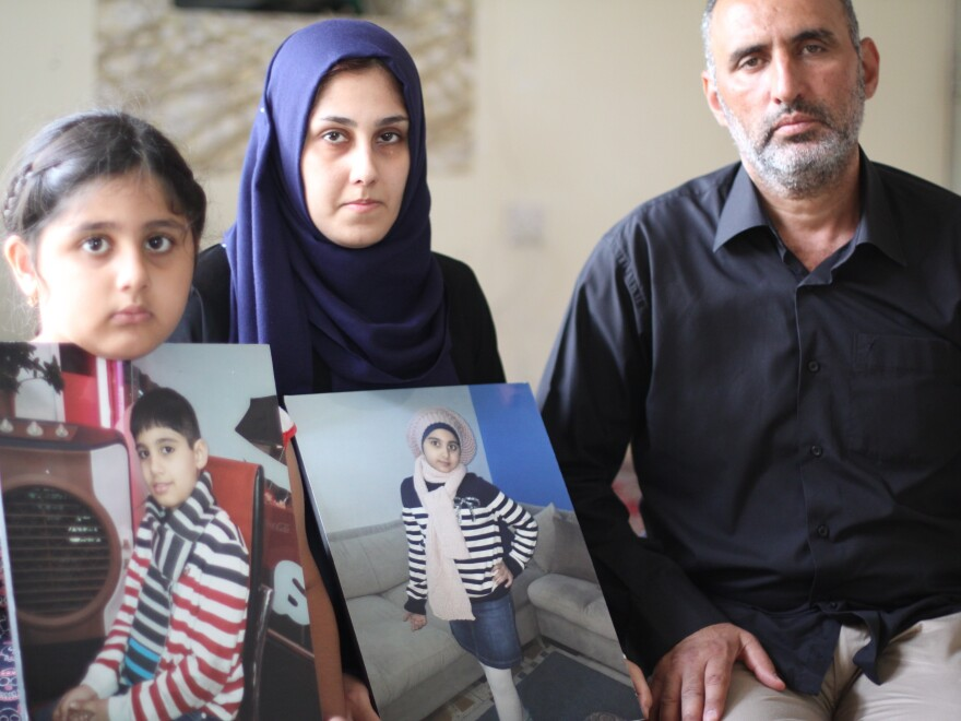 Zainab Abbas, husband Ahmed Hadi Jawad and their surviving daughter, Rawan, show photos of 10-year-old Zainab and 9-year-old Haider. The two children perished after a wave swept over their boat crossing the Aegean last week — the same boat carrying 3-year-old Aylan Kurdi and his family.