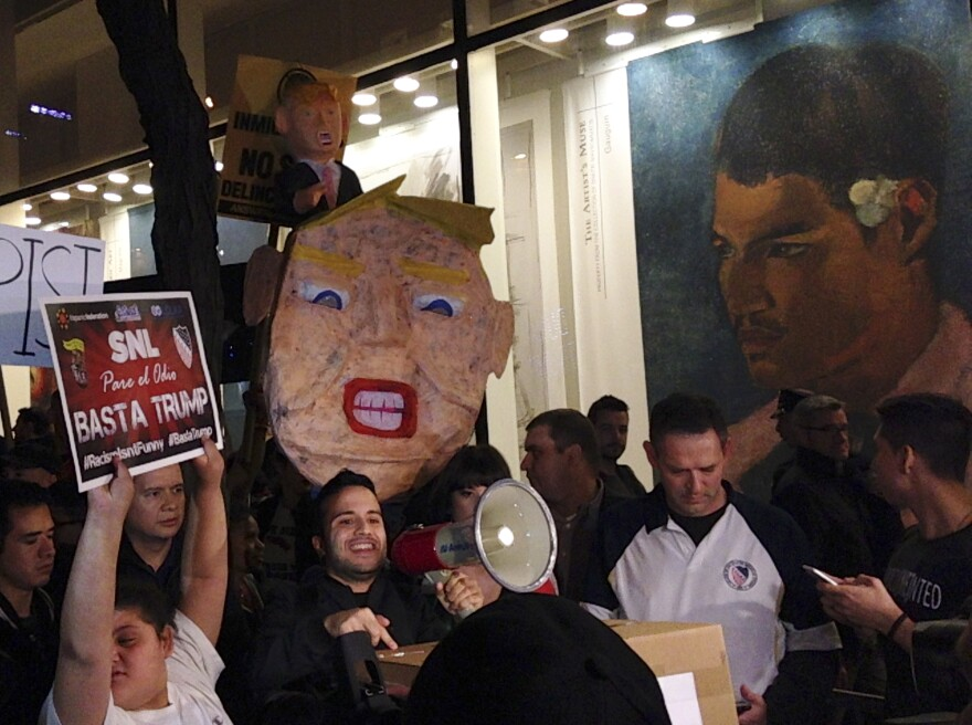 "Demonstrators march to protest Donald Trump's views on Latinos hours before he hosts ""Saturday Night Live,"" on Saturday in New York."