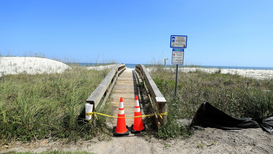 "Police tape and pylons block the public access to Jacksonville Beach last month amid the coronavirus outbreak. The mayor of Jacksonville, Fla., says parks and beaches in Duval County would reopen Friday for ""essential activities"" only."
