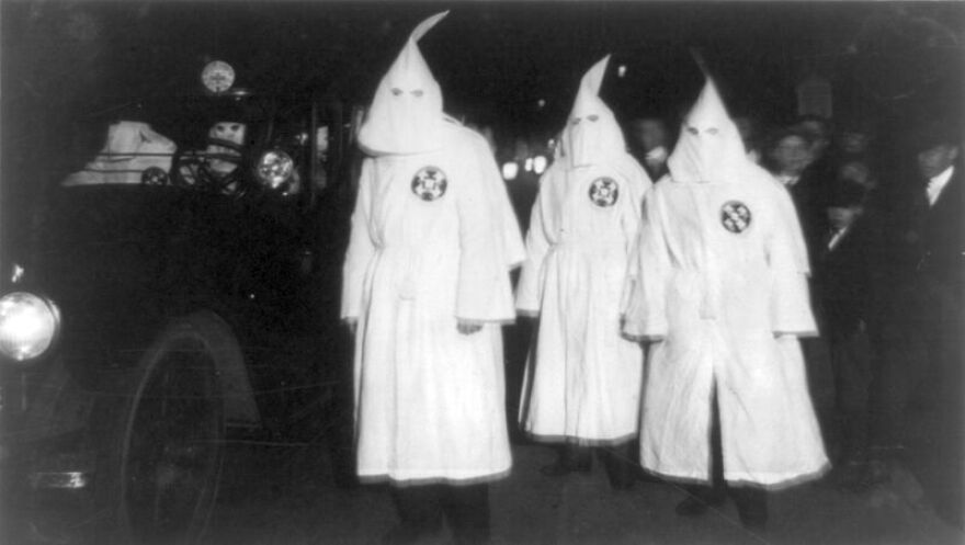Three Ku Klux Klan members standing beside an automobile driven by Klan members at a Ku Klux Klan parade through counties in Northern Virginia bordering on the District of Columbia.