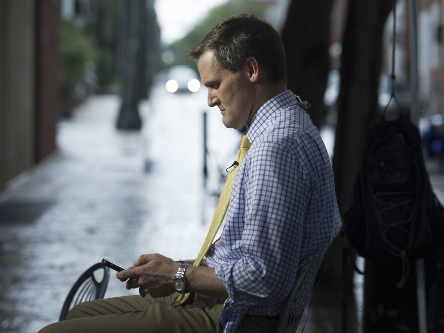 Mike Signer, mayor of Charlottesville at the time, checks his phone while waiting to speak days after Heather Heyer was killed during the Unite the Right rally in 2017. These days Signer travels the country presenting his city's experience as a cautionary tale.