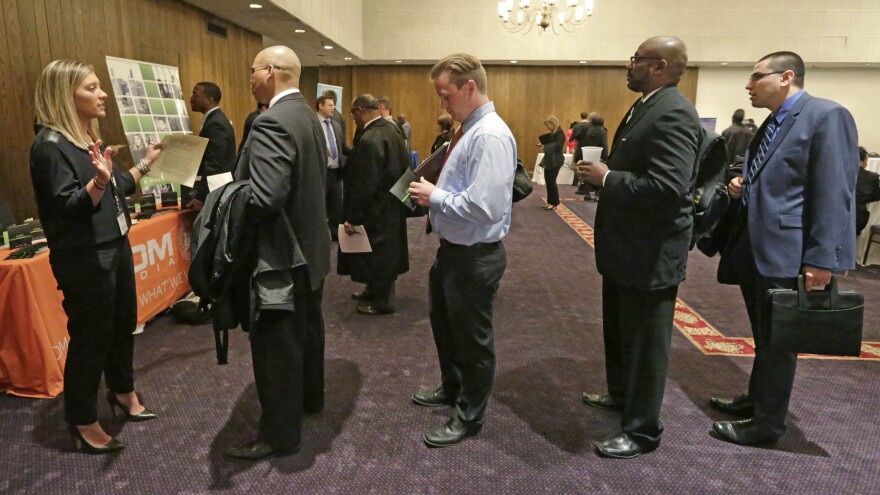 Bianca Medici (left), a corporate recruiter for CDM Media, speaks with job applicants during a Chicago job fair in May. The economy added 223,000 jobs in June, and unemployment fell to its lowest rate since 2008.