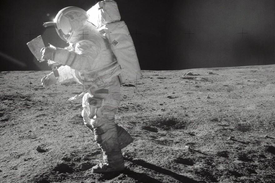 Astronaut Edgar D. Mitchell, Apollo 14 Lunar Module pilot, moves across the lunar surface as he looks over a traverse map during extravehicular activity (EVA). (NASA)