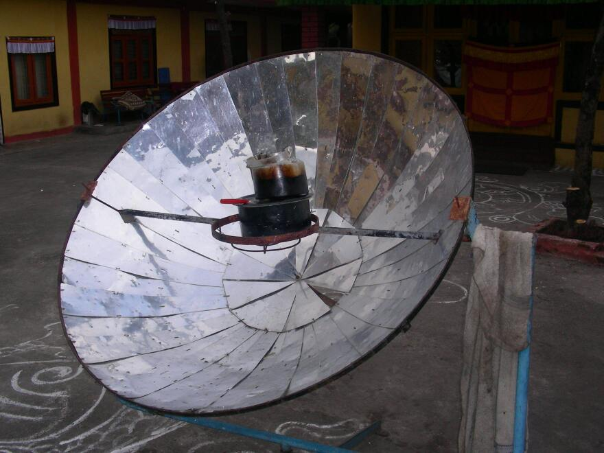 A parabolic solar cooker heats up a tea kettle in Nepal.