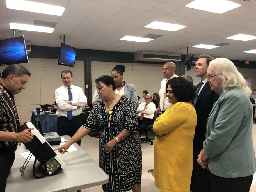 Trustee Debra Guerrero tries out Bexar County's new voting machine at a San Antonio ISD board meeting July 15, 2019.