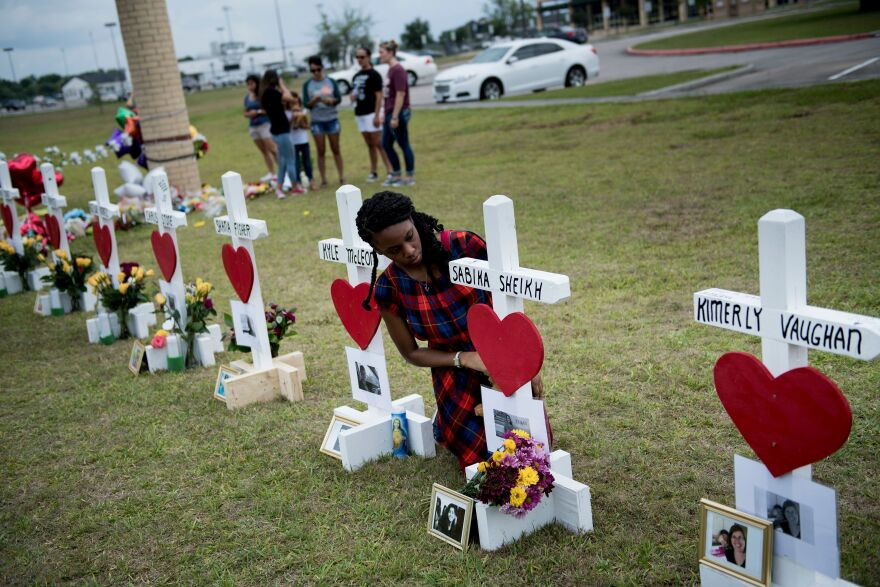 Jai Gillard, who was in the class where the mass shooting started, looks at a cross for Sabika Sheikh, an exchange student from Pakistan, before signing it at a memorial for the victims of the Santa Fe High School shooting in Texas.