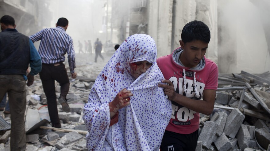 A Syrian woman is evacuated after being wounded in shelling by regime forces in the Shaar neighborhood of the northern Syrian city of Aleppo, on Oct. 13, 2012.
