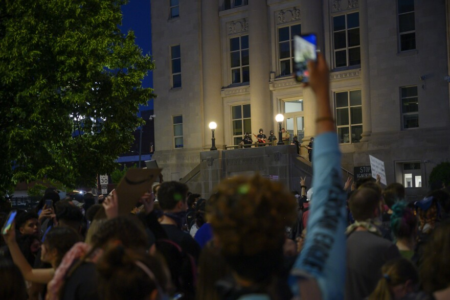 In a crowd of protesters, one arm reaches above them all with a phone taking a picture of police in the background.