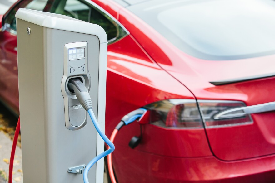 A large cable is plugged into an electric charging station at one end and a car at the other.