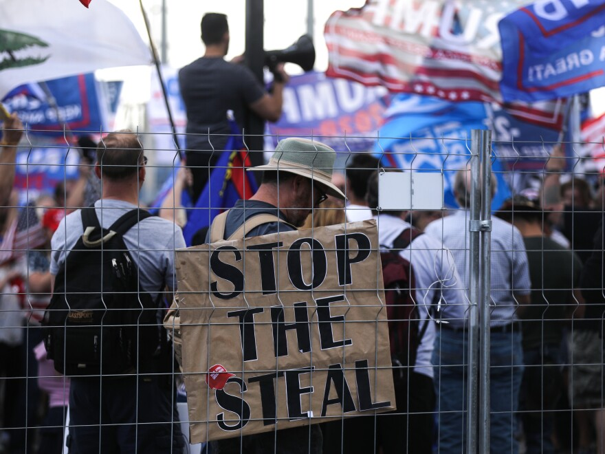 """Supporters of President Trump demonstrate at a """"Stop the Steal"""" rally in front of the Maricopa County Elections Department office in Phoenix on Saturday. Domestic terrorism analysts warn that a prolonged fight and Trump's statements about the vote only fuel polarization."""