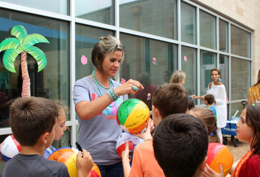Comal ISD's Garden Ridge Elementary Principal Jennifer Schultz signs autographs on her students' beach balls. Schultz said Garden Ridge ended the school year May 30, 2019 with 70 more students than they had the previous fall.