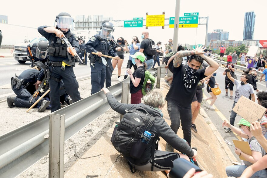 An Austin police officer points a shotgun equipped to fire so-called less lethal rounds at a demonstrator on I-35 in downtown Austin on May 30.