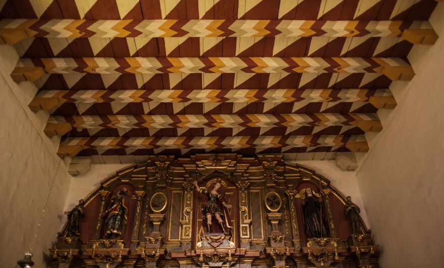 The interior of Mission Dolores, showing the ceiling from the front door to the back wall, painted in a traditional basket-weave pattern, while the walls are painted in a Baroque style, covered in saints and gold.
