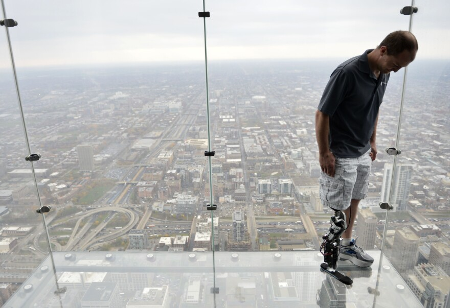 "Zac Vawter, fitted with an experimental ""bionic"" leg, looks down from the Ledge at the Willis Tower, on Thursday in Chicago."
