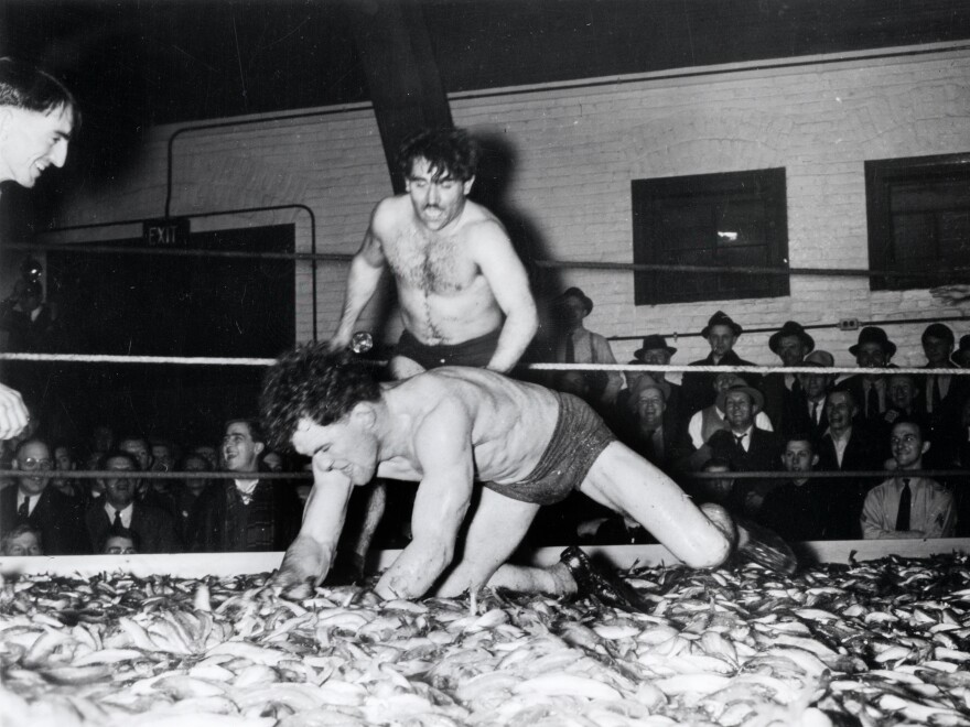 Two men wrestle in a ring full of smelt during the Smelt Carnival in Marinette, Wis., in 1939.