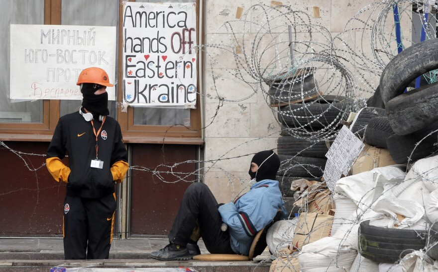 "Masked pro-Russian activists guard a barricade at an occupied regional administration building in Donetsk, Ukraine, Saturday. Ukraine says it is suspending an ""anti-terrorist"" operation for Easter."