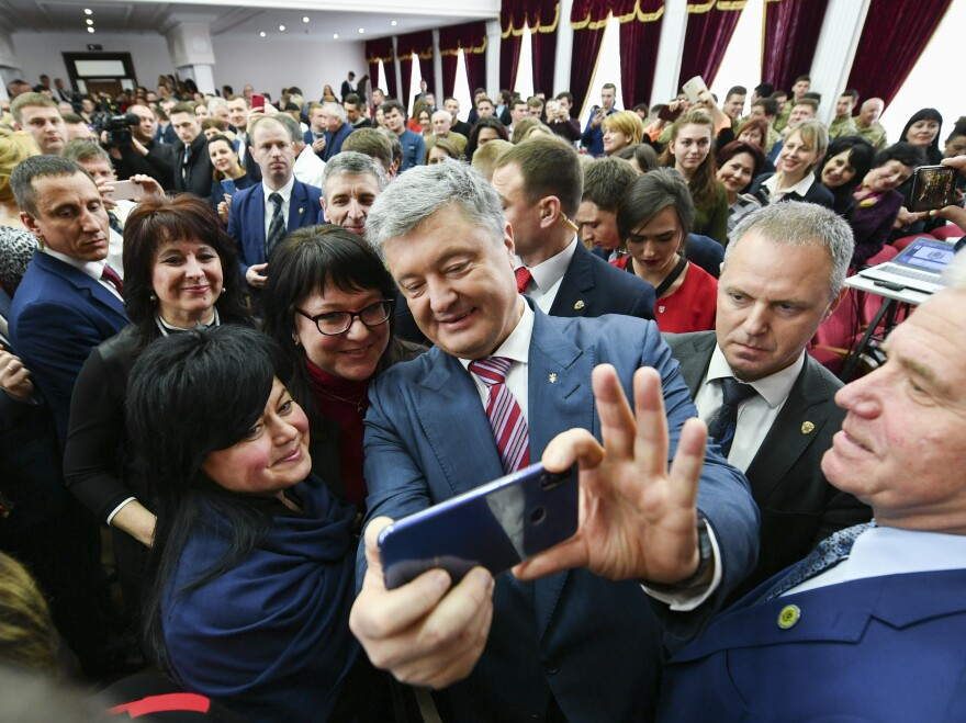 Ukrainian President Petro Poroshenko takes a selfie with students in Kiev, Ukraine, on March 25. He is struggling for second place against veteran politician Yulia Tymoshenko.