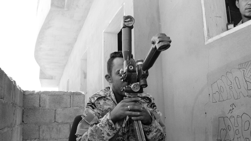 A Libyan soldier peers across the frontline in Sirte during battle against the Islamic State in 2016.