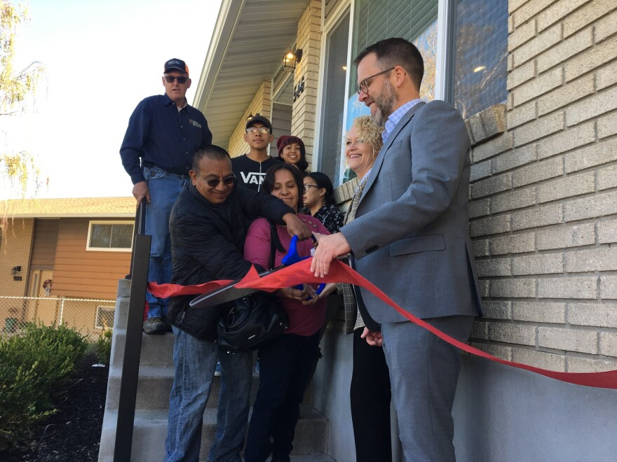 Photo of a man cutting a ribbon in front of his house.