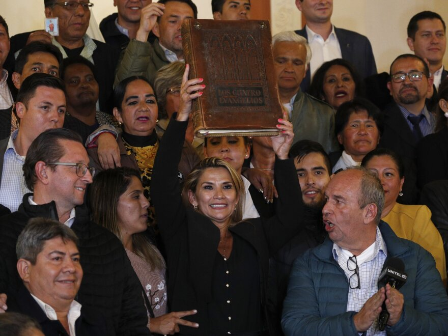 Surrounded by fellow lawmakers, Jeanine Añez holds a Bible after she declared herself the interim president of Bolivia on Tuesday.