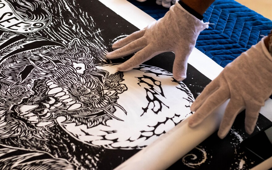 """Curators unfurl artist Andy Ritzo's image titled """"The Tyger,"""" in preparation for the BIG INK exhibition. Thomas Iacobucci/WUSF Public Media"""