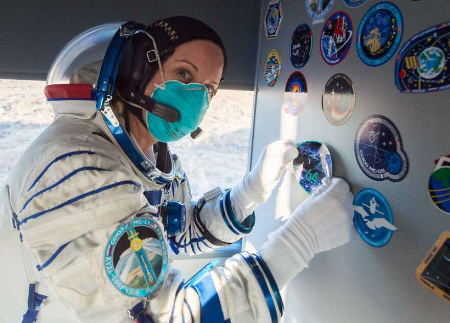 Expedition 64 NASA astronaut Kate Rubins affixes an Expedition 64 sticker inside the bus carrying her and fellow crewmates Russian cosmonauts Sergey Kud-Sverchkov and Sergey Ryzhikov of Roscosmos to the launch pad, Wednesday, Oct. 14, 2020, at the Baikonur Cosmodrome in Kazakhstan. The trio launched at 1:45 a.m. EDT to begin a six-month mission aboard the International Space Station. Photo: (NASA/GCTC/Andrey Shelepin)