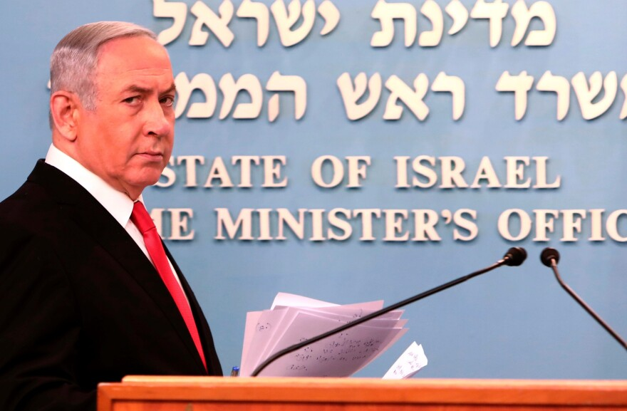 Prime Minister Benjamin Netanyahu approaches the podium to give a speech from his Jerusalem office on Saturday, saying Israel's restaurants and places of entertainment will be closed to stop the spread of the coronavirus. He also encouraged people not to go to their workplaces unless absolutely necessary.