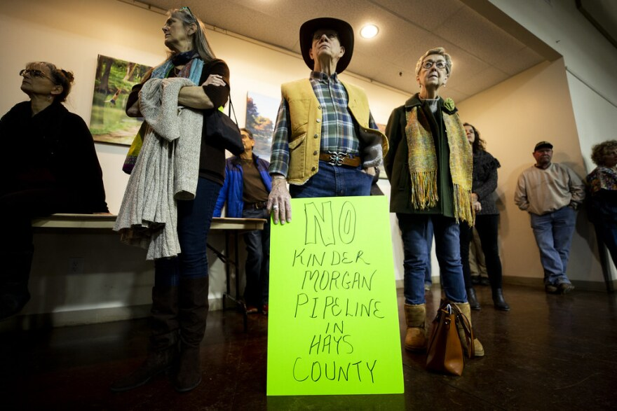 A protester holds a sign against the Kinder Morgan pipeline project