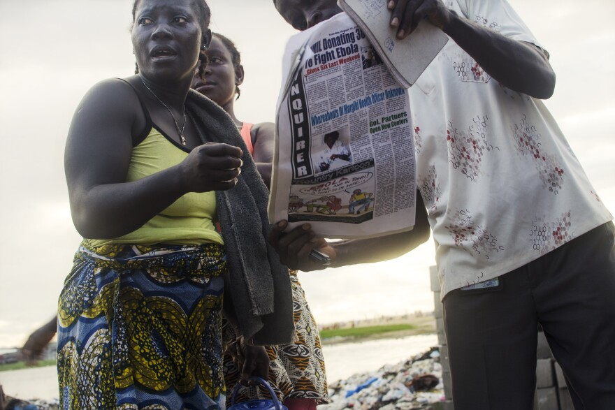 Residents of West Point read newspaper articles about the Ebola-related unrest in their community.
