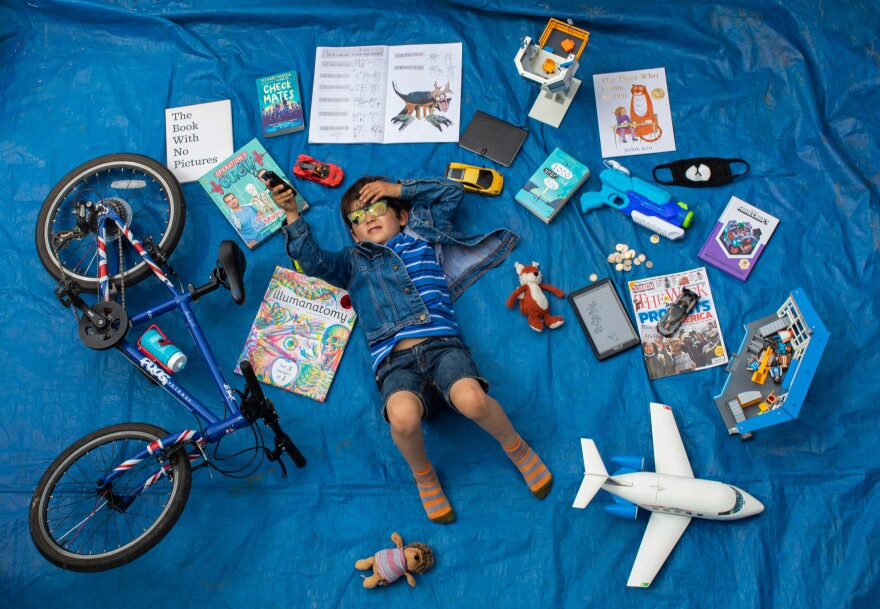 Elizabeth Dalziel's son Joe, 7, lays next to his favorite objects, toys and books as part of a homeschooling assignment — to create a time capsule — from his school in Berkhamsted, England.