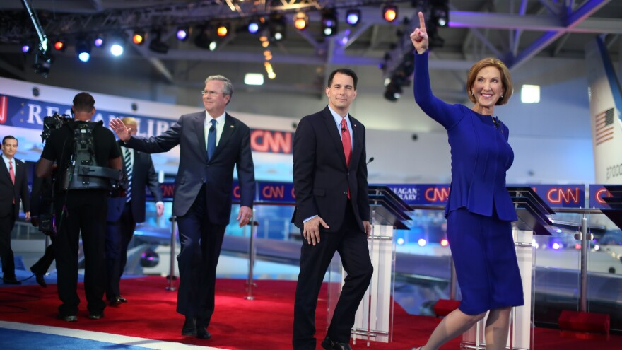 Republican presidential candidate Carly Fiorina walks onstage followed by Scott Walker, Jeb Bush and other candidates in Wednesday's debate.