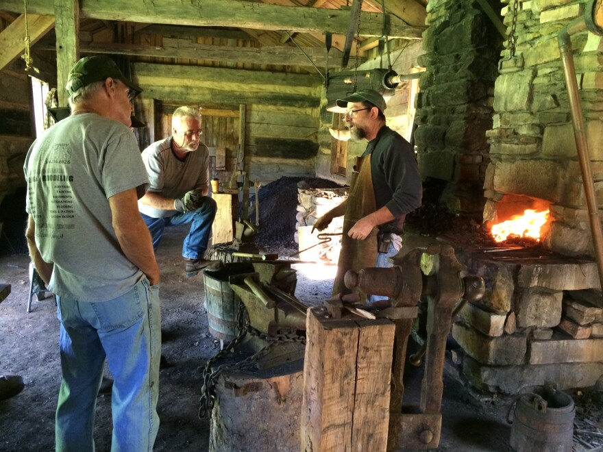 Ed Harris and Jim Mays pay close attention as Greg Bray demonstrates blacksmithing techniques.