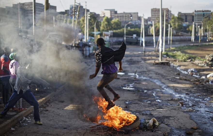 An opposition protester jumps over a burning barricade during clashes with police Thursday in the Mathare area of Nairobi, Kenya.