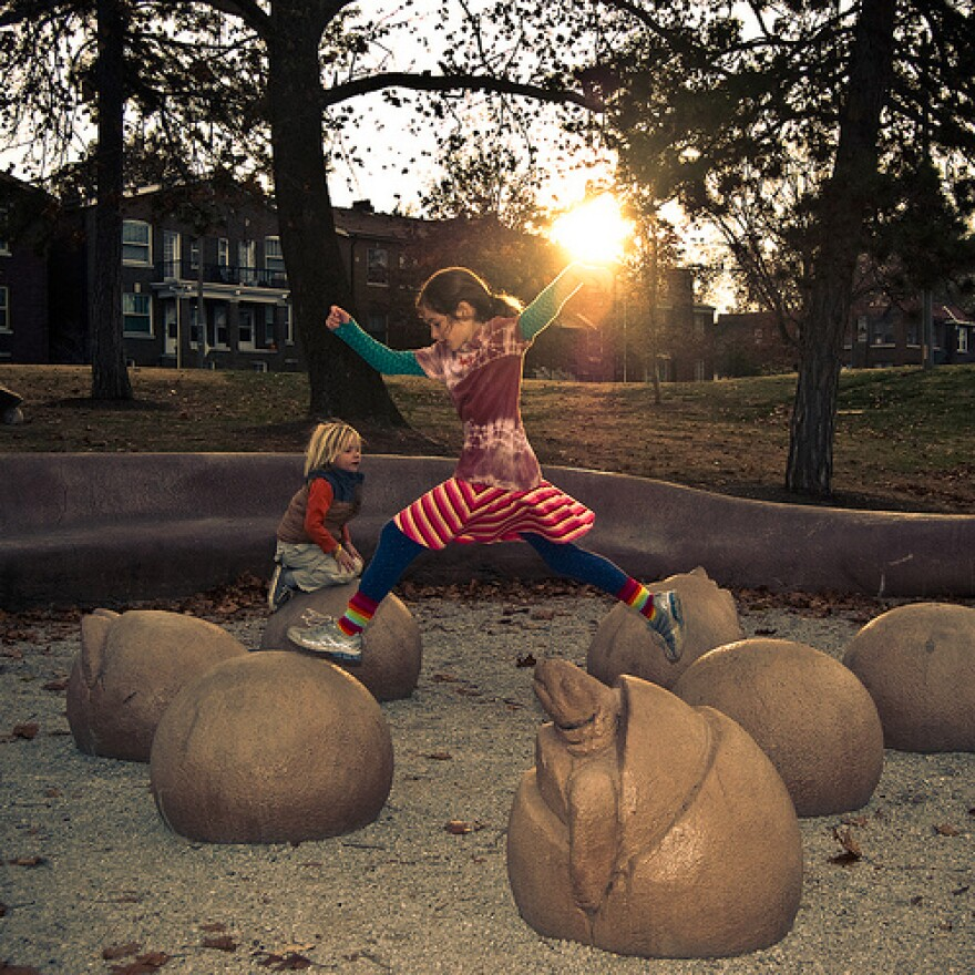 Girl leaping with setting sun in background