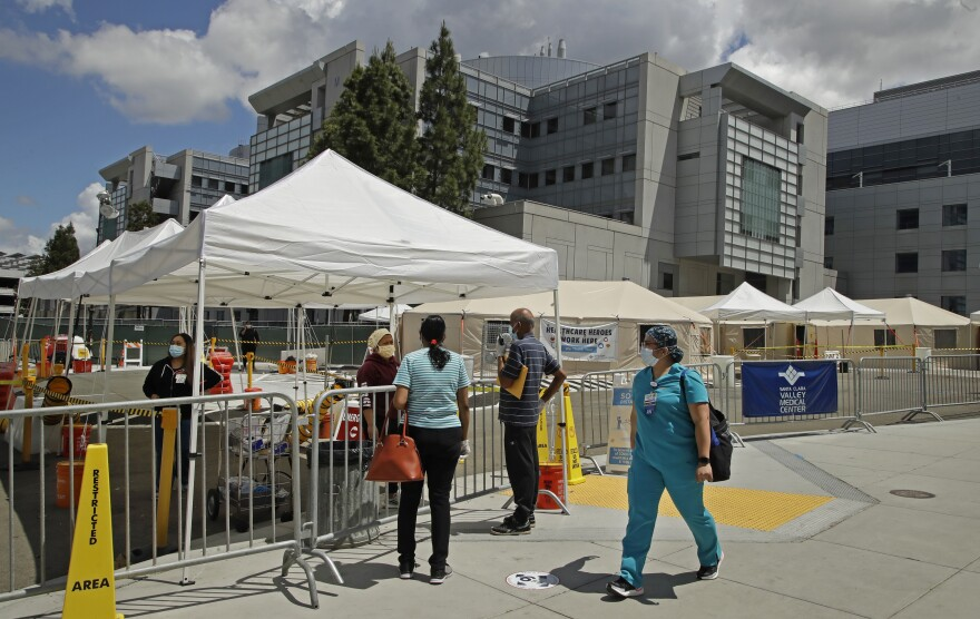 A health care worker walks past people waiting to be tested for COVID-19 at Santa Clara Valley Medical Center in San Jose, Calif., on May 19.
