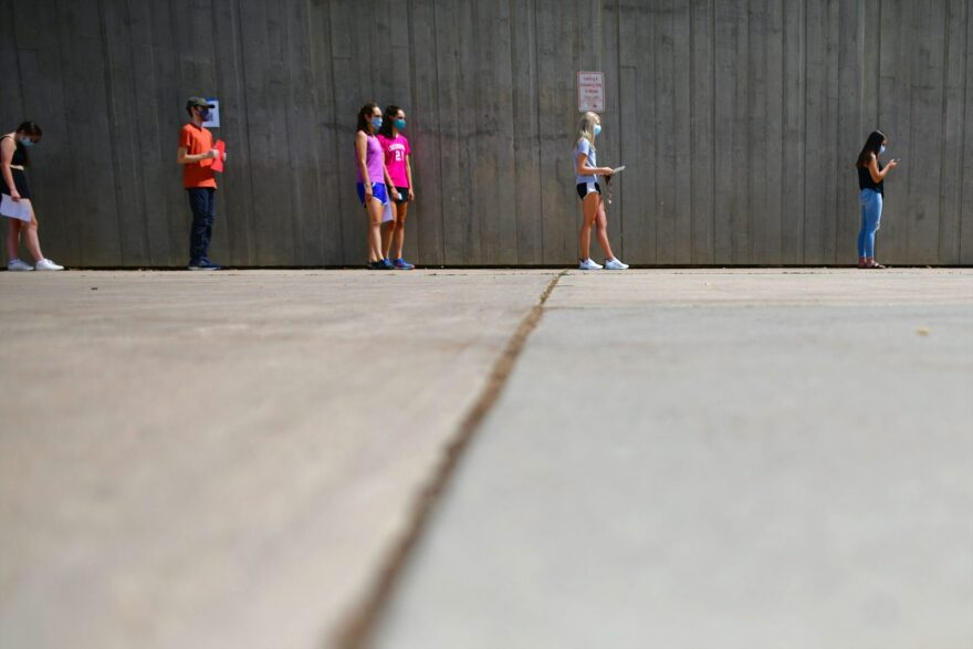 Students wait in line for registration and an identifying wristband after receiving a negative test result for coronavirus while arriving on campus at Colorado University in Boulder, Colorado.
