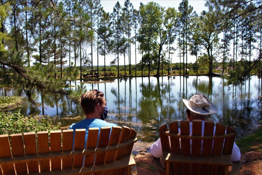Dietz Fischer and Mark Wieser chat next to a pond behind Das Peach Haus.
