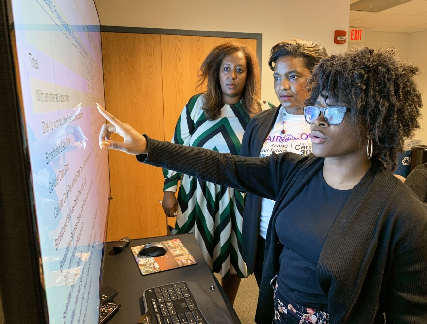 Cece Huddleston (right), an intern with the Congressional Black Caucus Foundation, reviews a dataset during a training session to make census outreach maps led by Jeanine Abrams McLean (center), Fair Count's vice president, and Menna Demessie, the foundation's vice president of research and policy analysis, in Washington, D.C.
