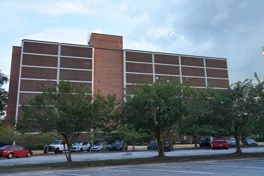 A large brick building overlooks a parking lot with trees and cars.